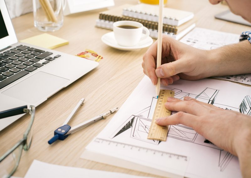 Side view of young architect using ruler and pencil to draw blueprint on wooden office desktop with stationery items, coffee cup and laptop keyboard